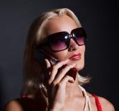 Attraktive glückliche Frau, die durch Mobile benennt Stockfotos