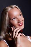 Attraktive glückliche Frau, die durch Mobiltelefon benennt Stockbild