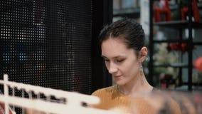 Attraktive glückliche junge Frau wählt am Speicher einige Waren auf Regalen Dekor für Hauptinnenraum Lizenzfreie Stockbilder