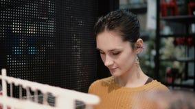Attraktive glückliche junge Frau wählt am Speicher einige Waren auf Regalen Dekor für Hauptinnenraum stock footage