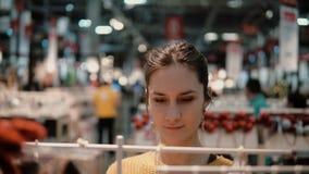 Attraktive glückliche junge Frau wählt am Speicher einige Waren Dekor für Hauptinnenraum stock footage