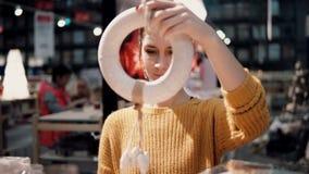 Attraktive glückliche junge Frau wählt am Speicher Weihnachtskranz Dekor für Hauptinnenraum Lizenzfreie Stockbilder