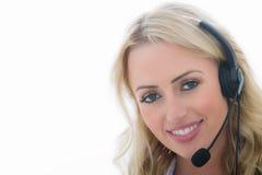 Attraktive glückliche junge Geschäftsfrau, die einen Telefon-Kopfhörer verwendet Stockfotos