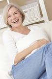 Attraktive glückliche ältere Frau, die zu Hause lacht Stockfotos