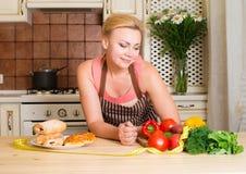 Attraktive Hausfrau, die zwischen gesundem Lebensmittel und Schnellimbiß wählt stockfotos