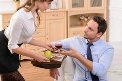 Attraktive Hausgehilfin, die mit Mann flirtet stockbild
