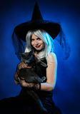 Attraktive Hexe mit einer Katze Stockfotografie