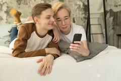 Attraktive internationale homosexuelle Paare, die im Bett vor Nachtschlaf sich entspannen und Smartphoneschirm betrachten stockfoto