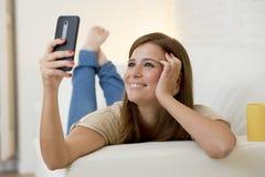 Attraktive 30 Jahre alte Frau, die auf der Hauptsofacouch nimmt selfie Porträt mit Handy spielen Lizenzfreie Stockbilder