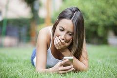 Attraktive Jugendliche, die einen überraschenden Text beim Lügen auf Gras empfängt Stockfotografie