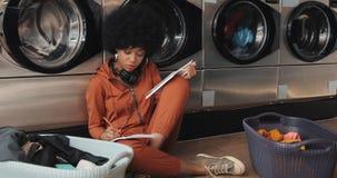 Attraktive junge Afroamerikanerfrau, die ein Buch liest und Anmerkung beim Waschen ihrer Wäscherei am Waschautomaten schreibt stock footage