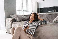 Attraktive junge afroe-amerikanisch Frau, die auf einer Couch sitzt stockfotos