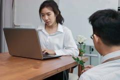 Attraktive junge Asiatin, die mit Laptop mit dem Geschäftsmann gibt eine weiße Rose im Büro an Valentinsgruß ` s Tag arbeitet Lie lizenzfreie stockbilder