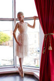 Attraktive junge Ballerina nahe einem Fenster lizenzfreies stockbild