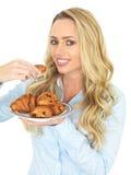 Attraktive junge blonde behaarte Frau, die ein dänisches Gebäck von einer Platte von Assorted Gebäck nimmt Lizenzfreie Stockfotos