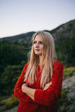 Attraktive junge blonde Frau auf dem Hintergrund des Berges und des Waldes Lizenzfreie Stockbilder