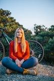 Attraktive junge blonde Frau auf dem Hintergrund des Fahrrades und des Waldes Lizenzfreies Stockbild