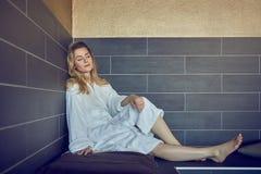 Attraktive junge blonde Frau, die auf einer Bank in einer Sauna sich entspannt Stockbild