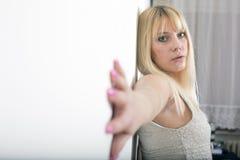 Attraktive junge blonde Frau, die auf Wand aufwirft Lizenzfreie Stockfotos