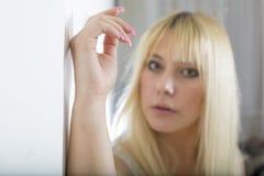 Attraktive junge blonde Frau, die auf Wand aufwirft Stockbild