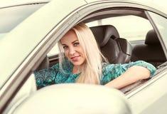 Attraktive junge blonde Frau, die im Auto sitzt Lizenzfreie Stockfotografie
