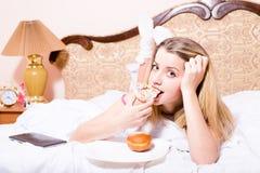 Attraktive junge blonde Frau, die im glace Donut weiße des Betts beißende Farbmit Tabletten-PC-Computer liegt u. Kamera betrachte Stockbilder