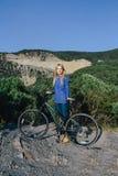 Attraktive junge blonde Frau, die mit dem Fahrrad auf den Hintergrundbergen steht Stockbild