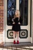 Attraktive junge blonde Frau, die schwarze Kleiderrot-Schuhe steht Lizenzfreie Stockfotos