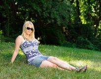 Attraktive junge blonde Frau, die sich draußen entspannt Lizenzfreie Stockfotos