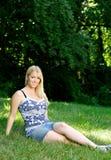 Attraktive junge blonde Frau, die sich draußen entspannt Stockbild