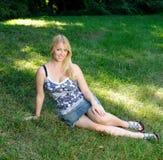 Attraktive junge blonde Frau, die sich draußen entspannt Stockbilder