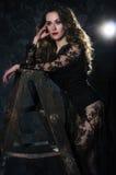 Attraktive junge blonde Frau in einem langen schwarzen Kleid steht O Stockfotos