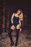 Attraktive junge blonde Frau in einem schwarzen Bodysuit, in einem gemeinsamen Badeanzug und in schwarzen Strümpfen, die in einem Stockfotografie