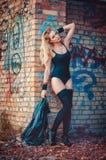 Attraktive junge blonde Frau in einem schwarzen Bodysuit, in einem gemeinsamen Badeanzug und in schwarzen Strümpfen, die in einem Stockbilder