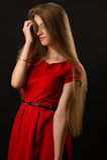 Attraktive junge blonde Frau im roten Kleid Stockbild