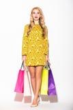 Attraktive junge blonde Frau mit Einkaufstascheweißhintergrund Lizenzfreie Stockfotografie