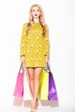 Attraktive junge blonde Frau mit Einkaufstascheweißhintergrund Stockfotografie