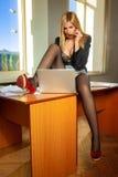 Attraktive junge blonde Geschäftsfrau, die im Büro arbeitet Stockfoto