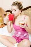 Attraktive junge blonde hübsche Frau, die in den Pyjamas auf trinkendem Getränk des Betts von der roten Schale u. vom beißende Fa Stockfotografie