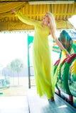 Attraktive junge blonde Modefrau im langen eleganten gelben Kleid im Vergnügungsparksommer lizenzfreies stockbild