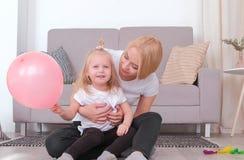 Attraktive junge blonde Mutter und ihre reizend Tochter, die zusammen mit rosa Ballon spielt Stockfotos