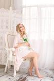 Attraktive junge blonde schwangere Frau, die auf Stuhl im weißen Nachthemd sitzt Sexy Mädchen des glücklichen Zaubers zu Hause Lizenzfreie Stockbilder