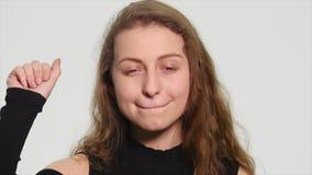 Attraktive junge Blondine, die ihre Hand in der Luft mit Aufregung und dem Lachen wellenartig bewegen stock video footage