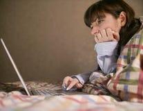 Attraktive junge brunette Frau, die auf dem Bett liegt und in ihrem Laptop arbeitet stockfotos