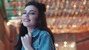 Attraktive junge Brunettefrau, die aufwirft und glücklich zur Kamera lächelt Spielerische Stimmung, seiend überzeugt Zeigen von G stock video