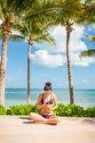Attraktive junge Brunettefrau in einem Bikini, der queresmit beinen versehenes vor einem weißen Sandstrand drinkin von einem fris stockfoto