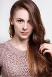 Attraktive junge Brunettefrau in einer gemütlichen Strickjacke Stockfotos
