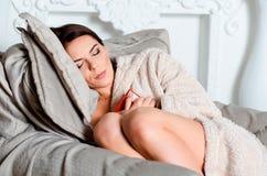 Attraktive junge Brunettefrau im Hauptbademantel, schlief an ein stockfotografie