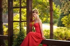 Attraktive junge dünne Frau im Park, Dame im roten Kleid und in den hohen Absätzen hat den Spaß und sitzt Stockbild