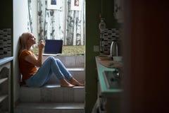 Attraktive junge Dame, die zu Hause heißes Getränk genießt stockfoto